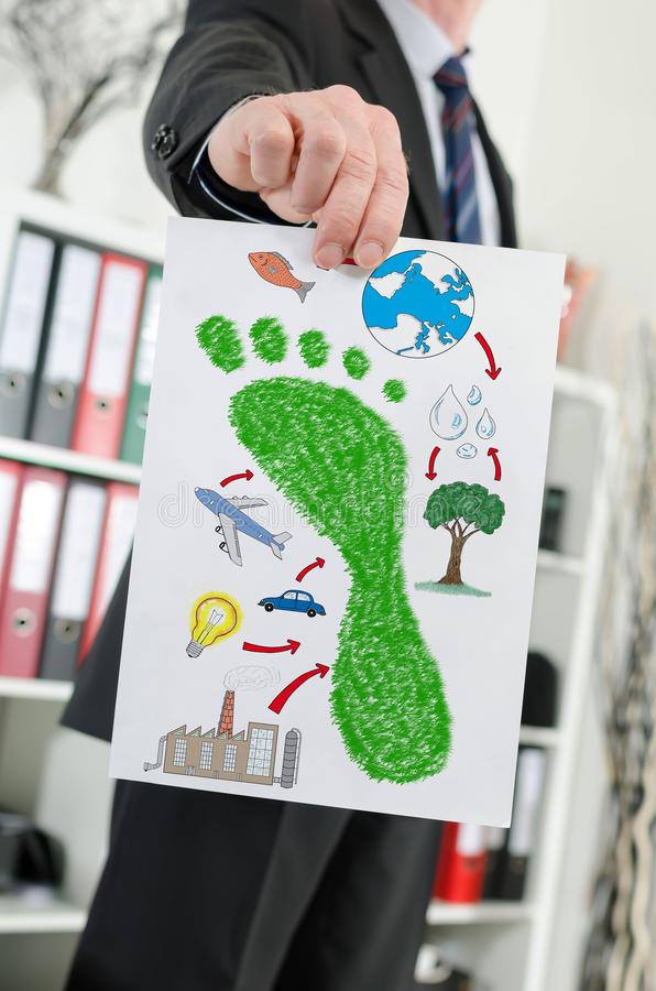 Carbon footprint concept shown by a businessman. Paper showing carbon footprint concept held by a businessman stock images
