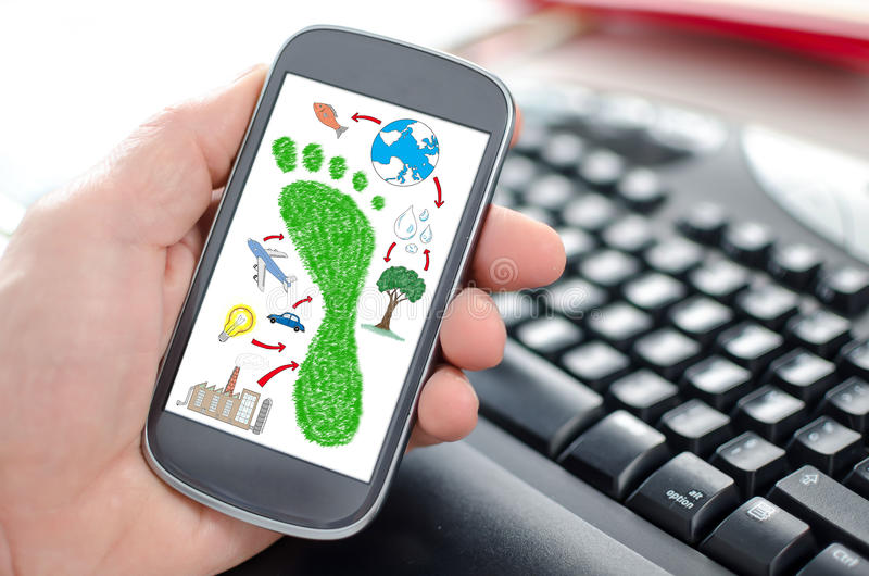 Carbon footprint concept on a smartphone. Hand holding a smartphone showing a carbon footprint concept stock photo