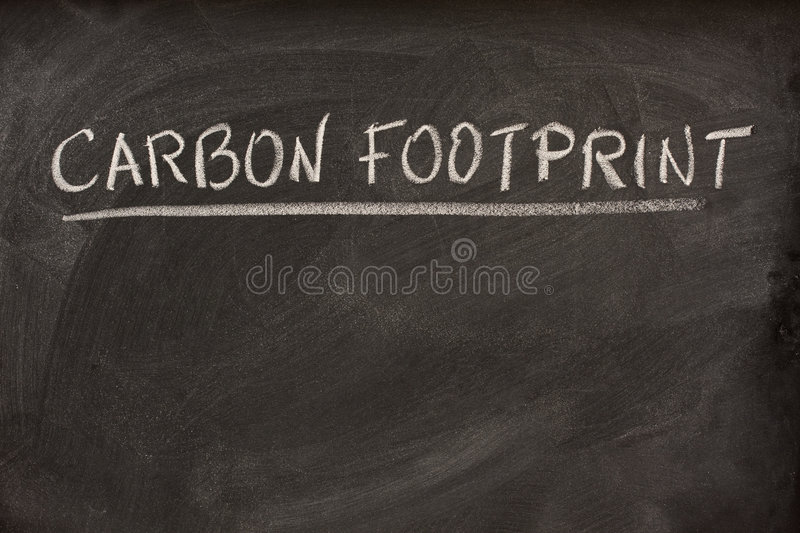 Carbon footprint title on a blackboard. Carbon footprint as lecture title or class topic handwritten with white chalk on a school blackboard royalty free stock photography