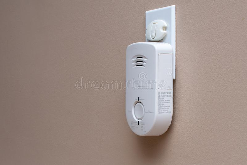Carbon Monoxide CO monitor plugged into the wall of a residential house for safety.  stock photo