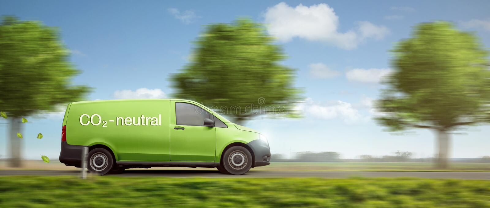 Carbon-neutral delivery with a green van driving on a country road with green trees royalty free stock photo