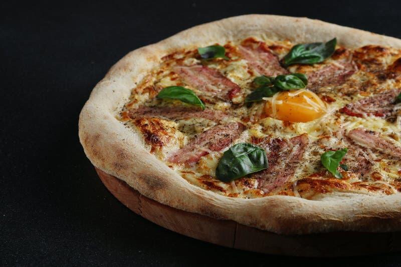 Carbonara比萨用烟肉和鸡蛋在黑暗的背景 免版税图库摄影