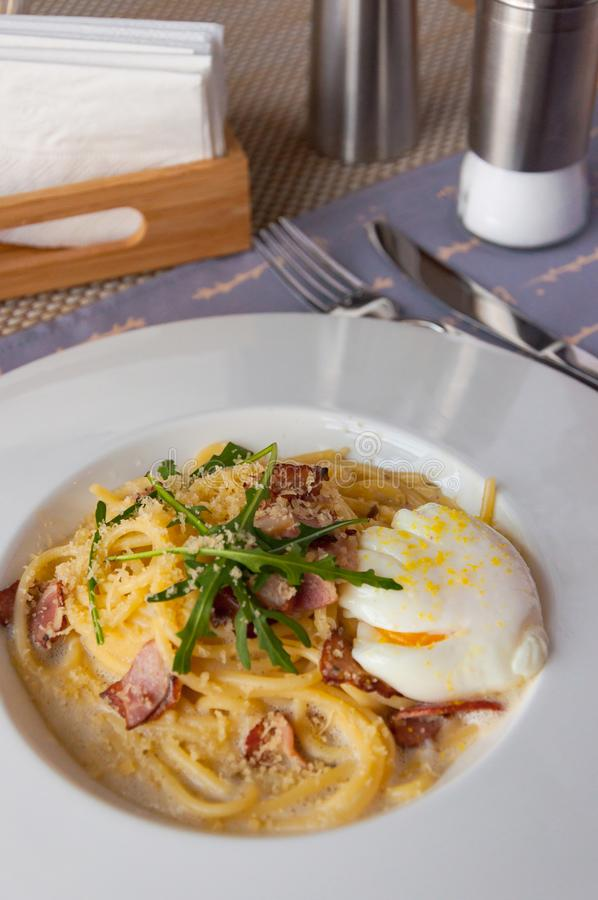 carbonara日光拍的意大利面食照片 意粉用烟肉、parsel和帕尔马干酪 在白色板材的面团Carbonara用在黑暗的巴马干酪 库存图片