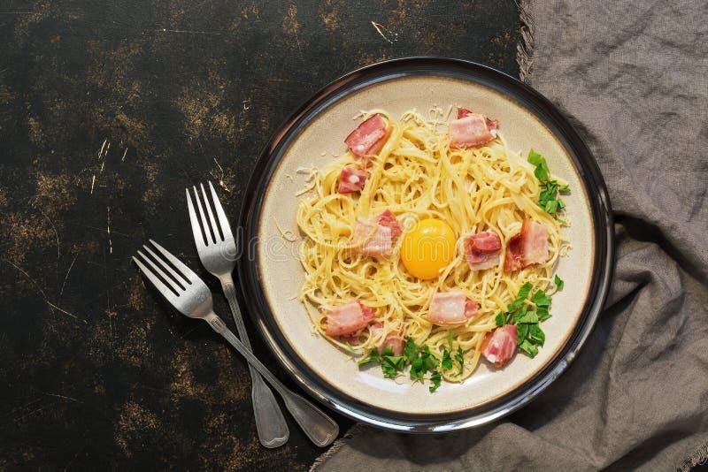 Carbonara de pâtes avec le parmesan, lard, jaune cru sur un fond rustique foncé Vue de ci-avant image libre de droits
