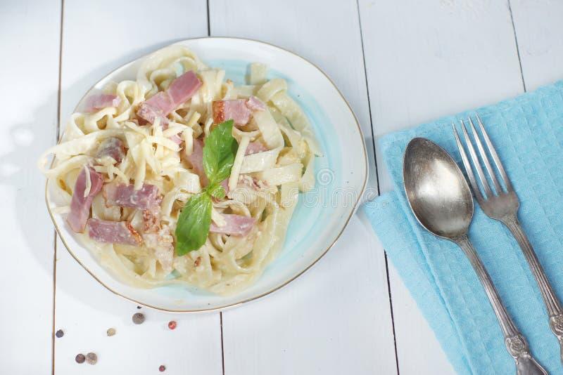 Carbonara de pâtes d'un plat avec des couverts près du plat, se tenant sur une table blanche en bois photographie stock libre de droits