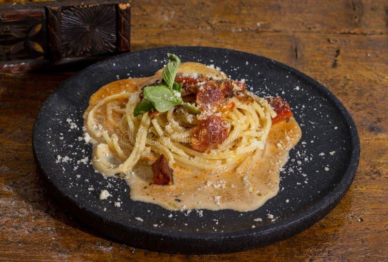 Carbonara degli spaghetti nel termine nero immagine stock