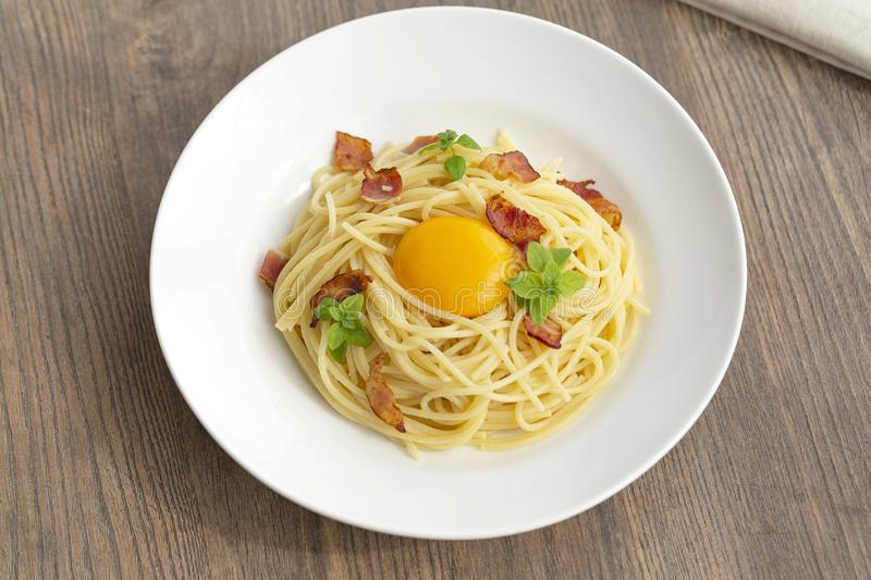 Carbonara pasta, spaghetti with pancetta, egg, hard parmesan cheese, basil and cream sauce. royalty free stock photography