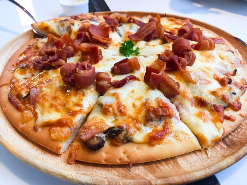 Carbonarapizza met Gerookte bacon, Ham, Paddestoel, van Cherry Tomato, van het Ei, van de Kaas en van de Room Saus die op de hout stock afbeelding