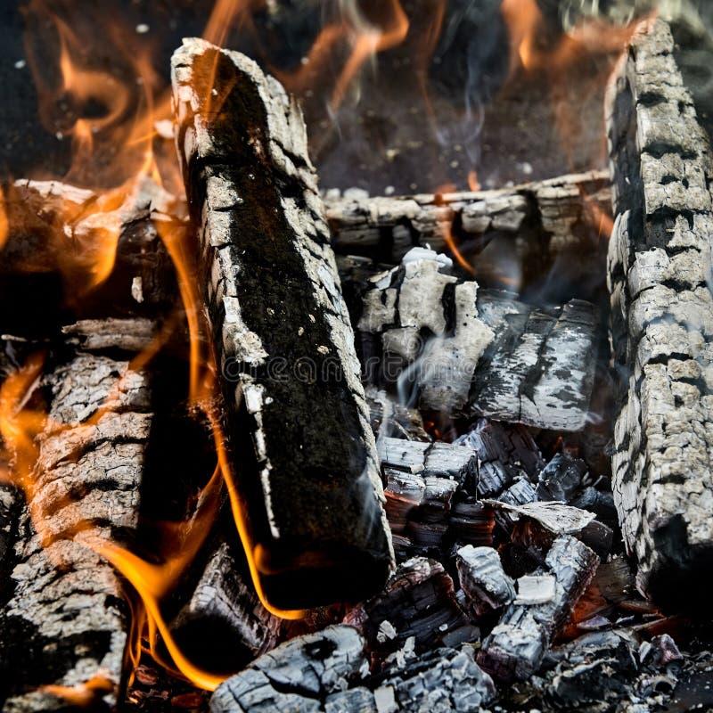 Carbones calientes y registros carbonizados de la madera en un fuego fotografía de archivo