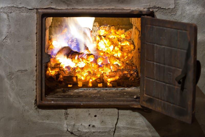Carbones de madera ardientes en un horno imágenes de archivo libres de regalías