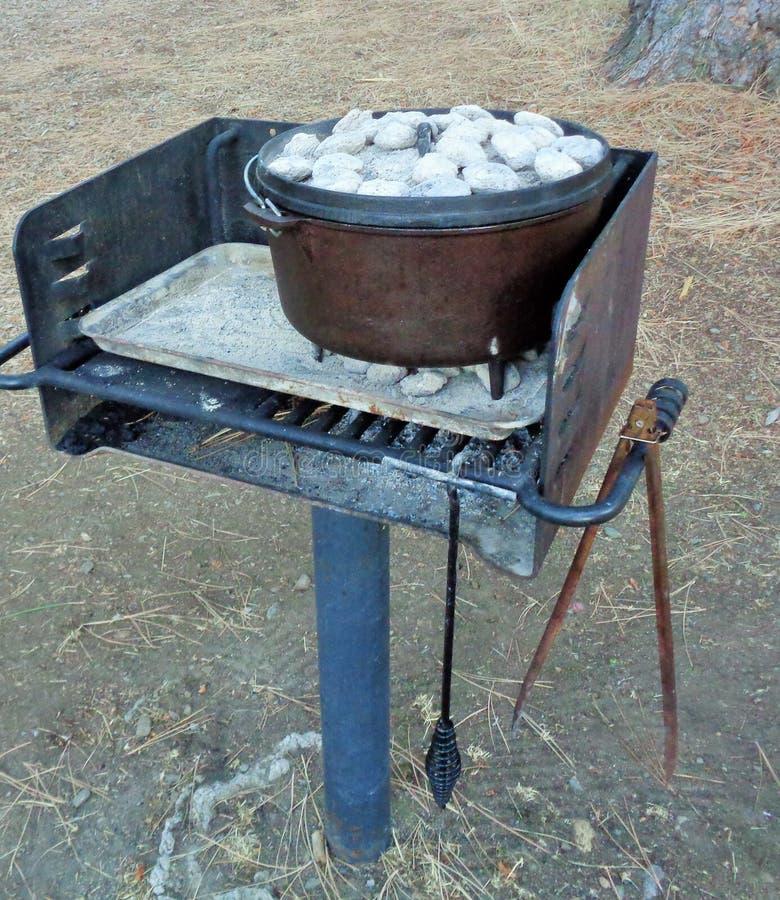 Carbones en la tapa de Oven Cooking Dinner holandés imagen de archivo