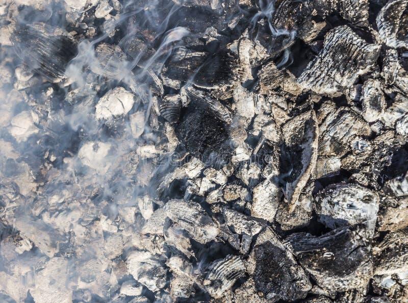 Carbones que arden y fuming imagenes de archivo