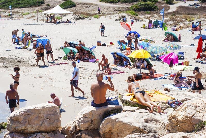 Carbonia Italien-AUGUSTI 10: Oidentifierat folk i vita strandwi royaltyfri bild