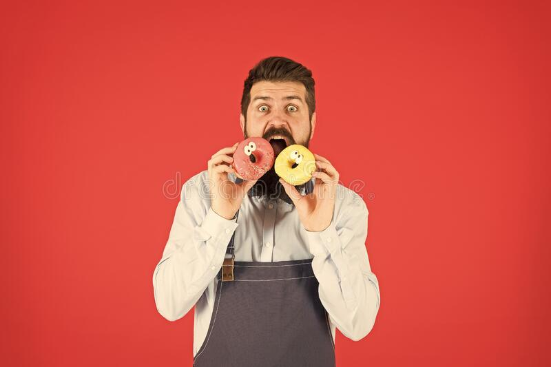 Carbs and calories. Bakery owner. Bakery business. Baked goods. Sweets and cakes. Junk food. Hipster bearded baker eat. Donuts. Doughnut bakery. Bearded royalty free stock photos