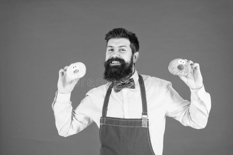 Carbs and calories. Bearded cheerful well groomed man selling donuts. Bakery owner. Bakery business. Baked goods. Sweets. And cakes. Junk food. Hipster bearded royalty free stock photography