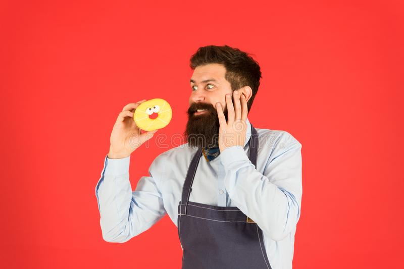 Carbs gluten diet. Bearded well groomed man in apron selling donuts. Donut food. Hipster baker hold donuts. Cheerful royalty free stock photography