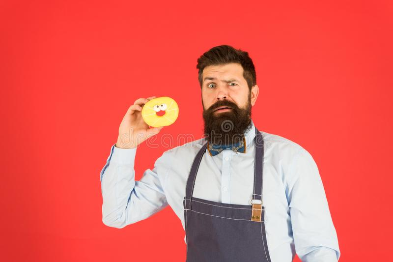 Carbs gluten diet. Bearded well groomed man in apron selling donuts. Donut food. Hipster baker hold donuts. Cheerful stock photo