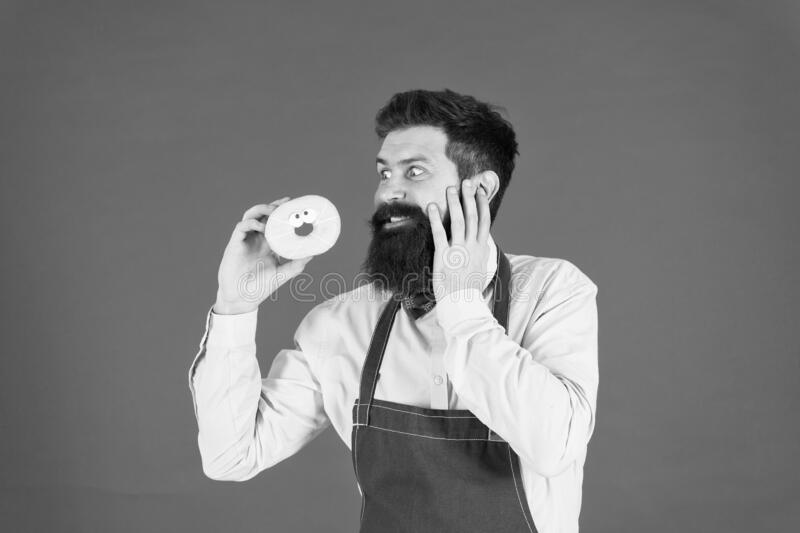 Carbs gluten diet. Bearded well groomed man in apron selling donuts. Donut food. Hipster baker hold donuts. Cheerful stock photography