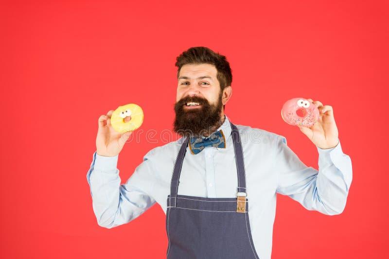 Carbs i kalorie Brodaci rozochoceni dobrze przygotowywający mężczyzny sprzedawania donuts Piekarnia w?a?ciciel Piekarnia biznes p fotografia royalty free