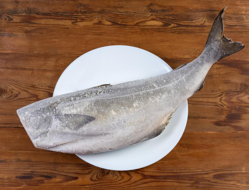 Carcass of frozen saithe without head on the rustic table. Frozen carcass of saithe, also known as coalfish without head on dish on the rustic table, top view royalty free stock photos