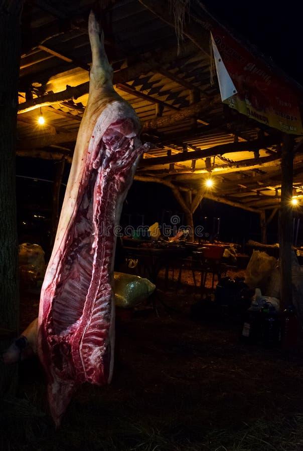 Carcasse de porc accrochant dans l'obscurité préparation au festival photo libre de droits