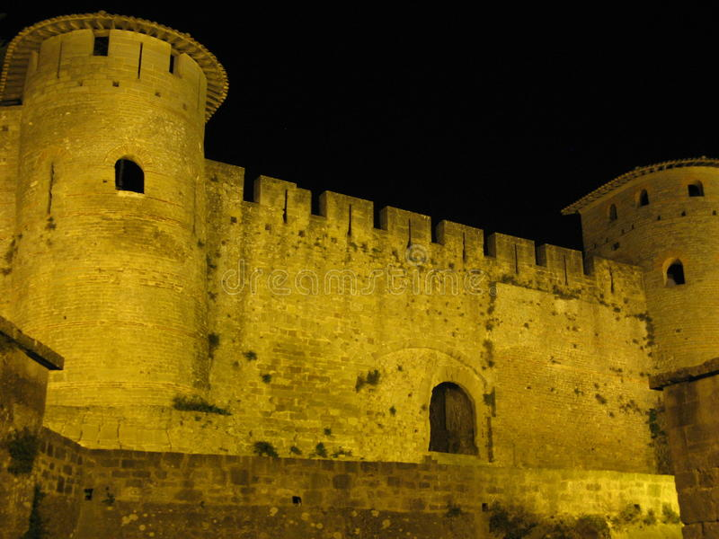Carcassonne Castle. In France at night with a view of the well lit walls, façade, towers and an entrance to the citadel royalty free stock images