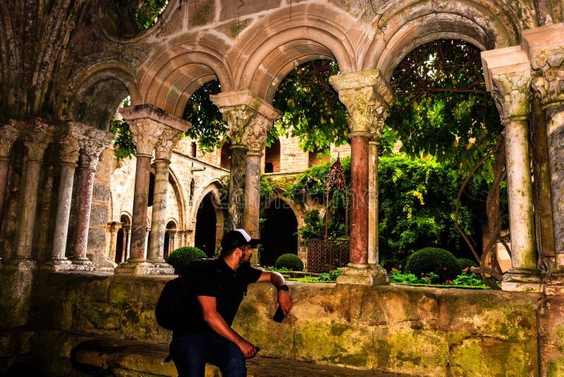 Carcassonne, França - 2019 Monastério da abadia de Fontfroide em França Turista masculino novo que olha o monastério gótico medie imagem de stock royalty free