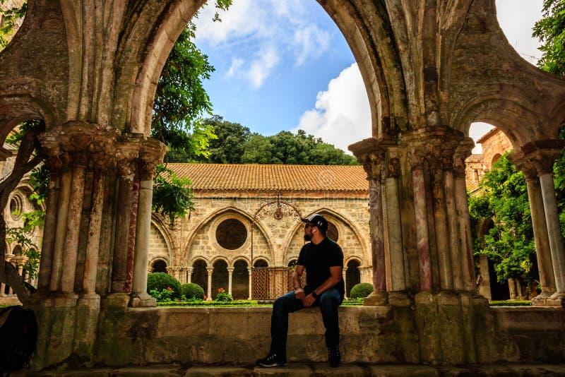 Carcassonne, Frankrijk - 2019 Het klooster van de Fontfroideabdij in Frankrijk Jonge mannelijke toerist die het middeleeuwse goti stock fotografie