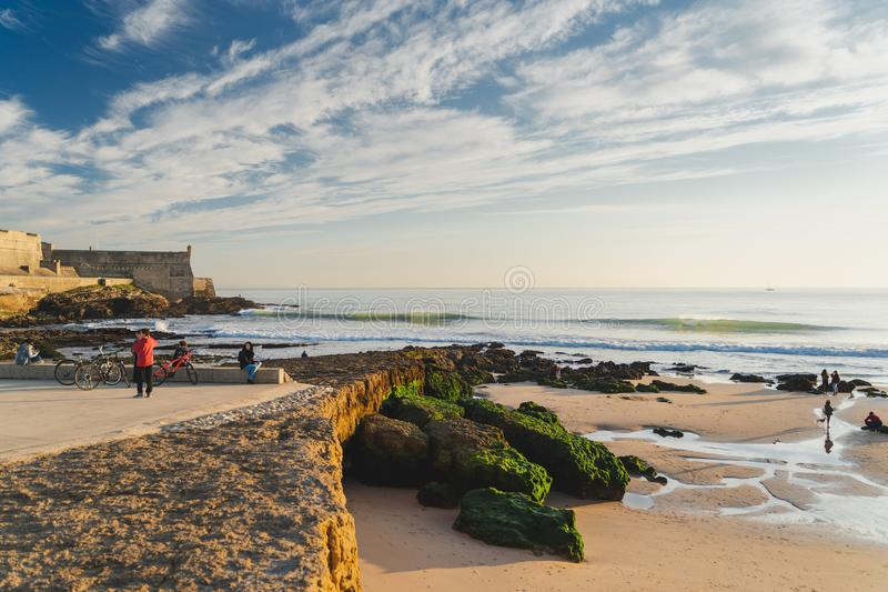 Carcavelos, Portugal - 12/31/18: Carcavelos beach and Saint Julian fortress. People enjoying the warm december sunset , small waves, rocks covered in green royalty free stock image