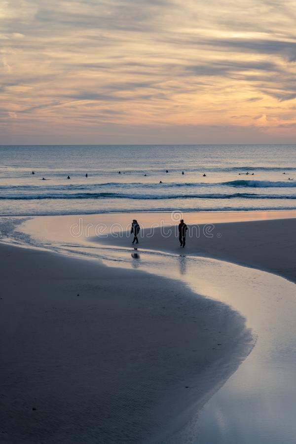 Carcavelos, Portugal - 12/23/18: Himmelreflexion im Wasserpool, das zum Ozean an Carcavelos-Strand bei Sonnenuntergang fließt lizenzfreie stockbilder