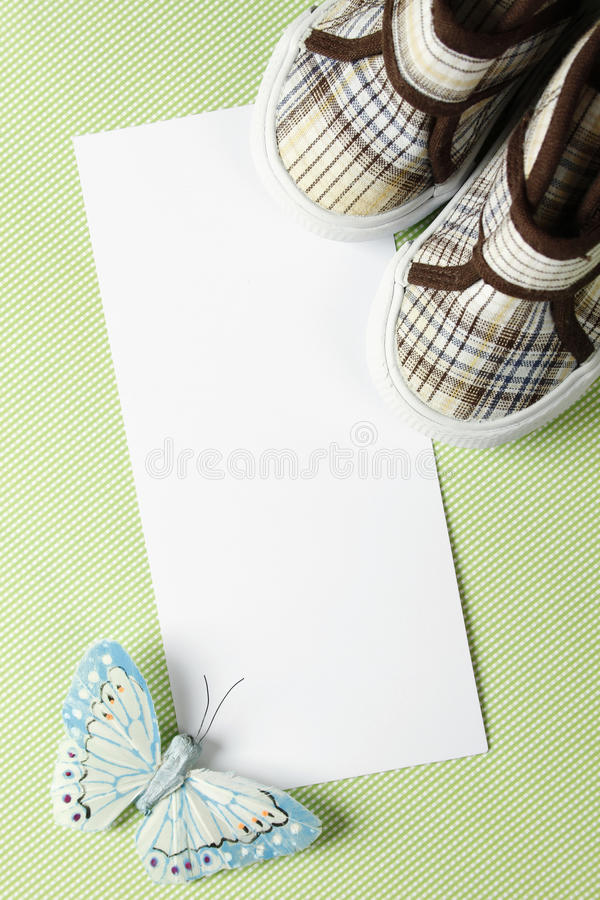 Card for birthday. Postcard for writing the text message of congratulations on his birthday or newborn shoes next to the child and the Butterfly Blue stock image