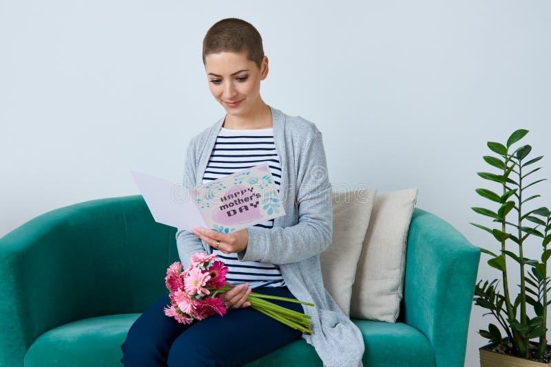 card den hållande buketten för barnmodern av gerberatusenskönor och läsning hennes dag för moder` s sammanträde på en soffa royaltyfria foton