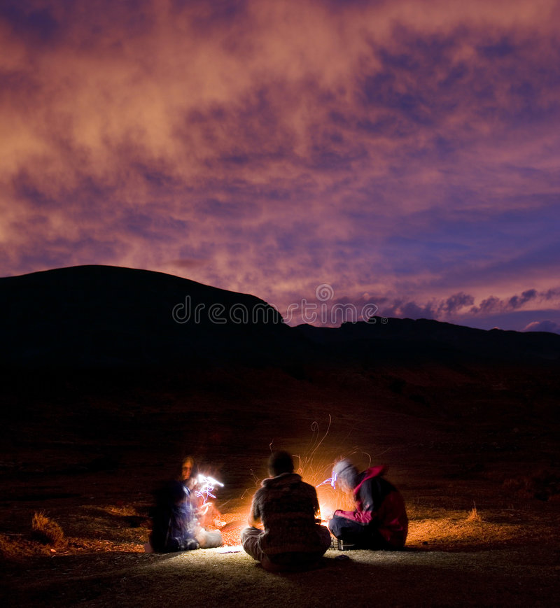 Card night. Purple clouds set against three campers playing cards in the mountains of Peru. Warm fire and sparks lighting the foreground