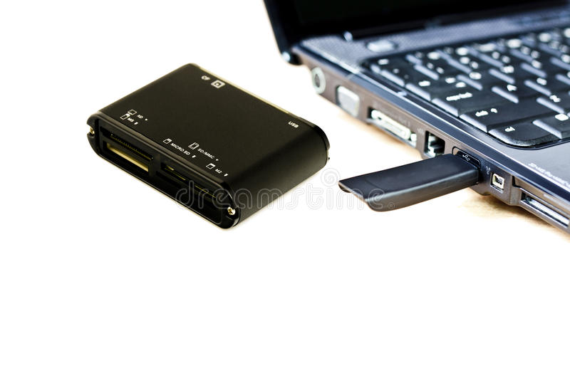 Card reader. A compact flash card reader with laptop at background stock photography