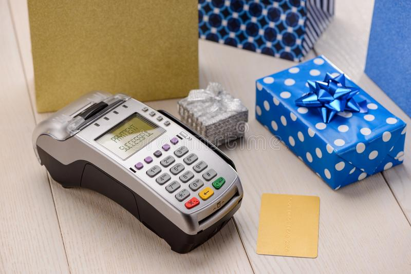 Card reader and gifts. Card reader, gift boxes and pockets on a wooden cash desk. Successful payment for a long list of holiday presents royalty free stock images