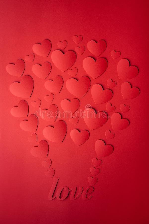 Card of red hearts, cut out of paper, laid out in the form of a balloon. The word love. stock photos