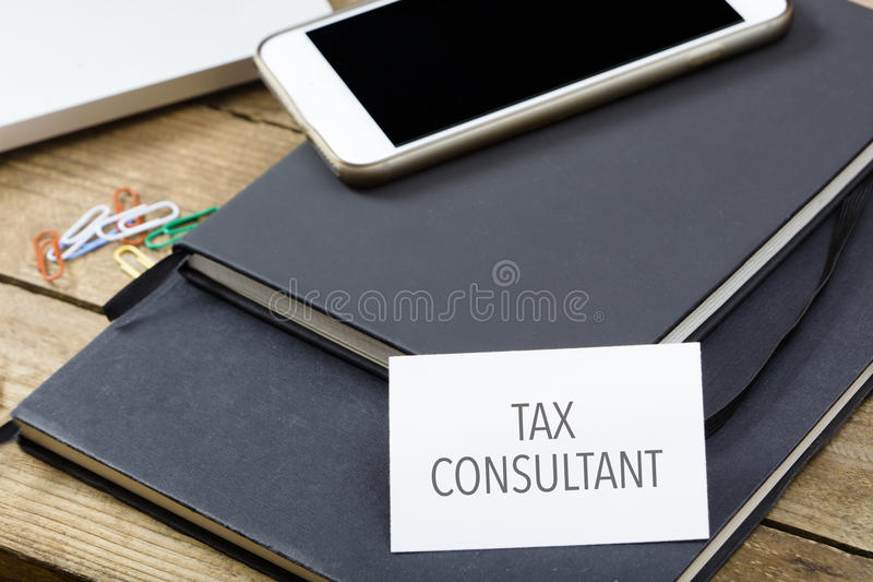 Card saying Tax Consultant on note pad. At desktop in office with laptop, tablet computer and phone stock photography