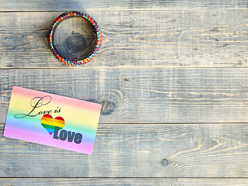 Card that says love is love with a rainbow background and a bracelet on hand with the LGBTQ flag LGBT lie on a light blue. Card that says love is love with a royalty free stock images