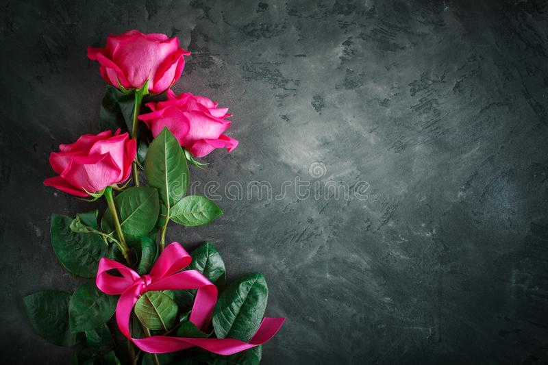 Card for St. Valentine`s Day, Mother`s Day. Day of Womans. Pink roses against a dark background. Background with copy space stock image