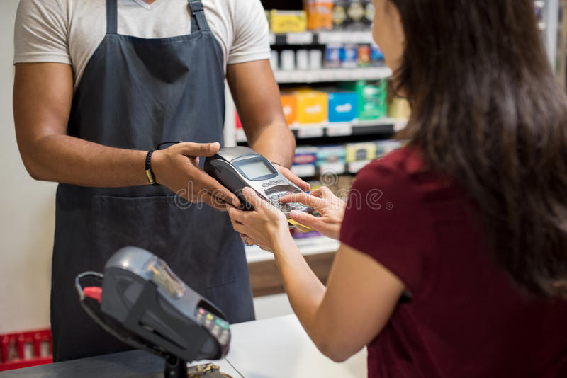 Card swiping machine at supermarket. Close up of woman's hand using credit card swiping machine to make payment. Woman entering credit card code in a card stock photos