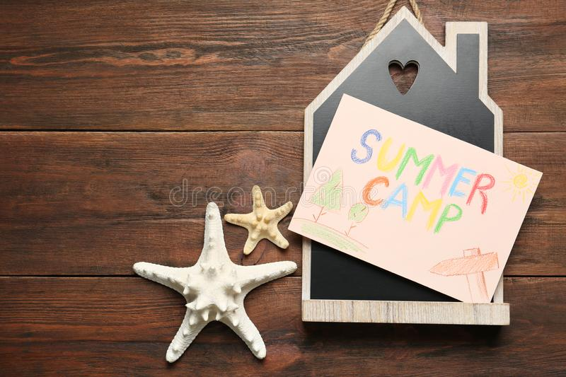Card with text SUMMER CAMP, starfishes and house model on wooden table. Flat lay stock images