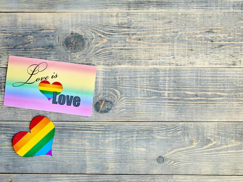 Card on which is written love is love with a rainbow background and a heart with the LGBT flag lie on a light blue textured wooden stock photos