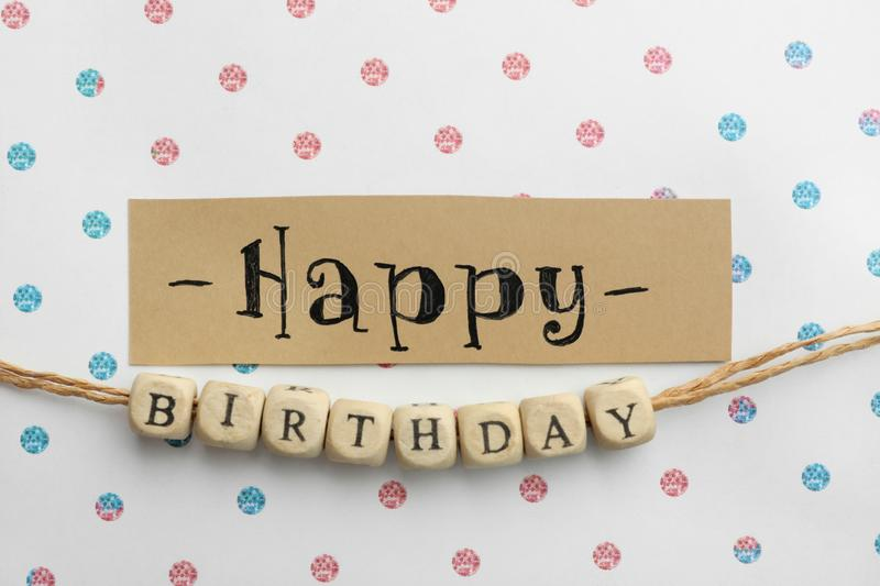 Card and wooden cubes with words HAPPY BIRTHDAY on paper with color pattern royalty free stock photos