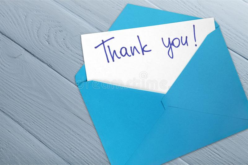 Thank you card and envelope on wooden background royalty free stock photography