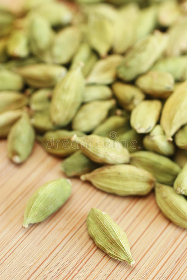 Cardamom. Close up of a cardamom seeds on wooden board royalty free stock photos