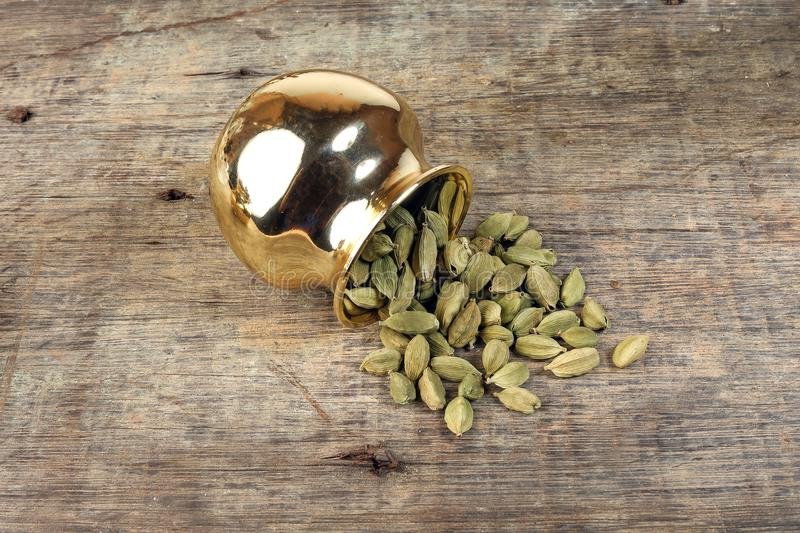 Cardamom spice in golden metal pot on rustic wood stock photography