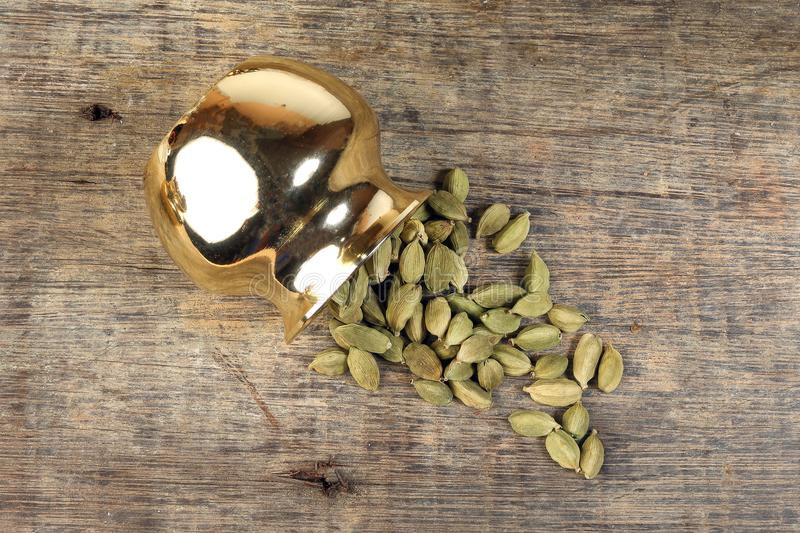 Cardamom spice in golden metal pot on rustic wood stock images