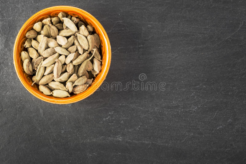 Cardamom. Whole Cardamom seeds in orange bowl on grey stone surface with copy space stock image