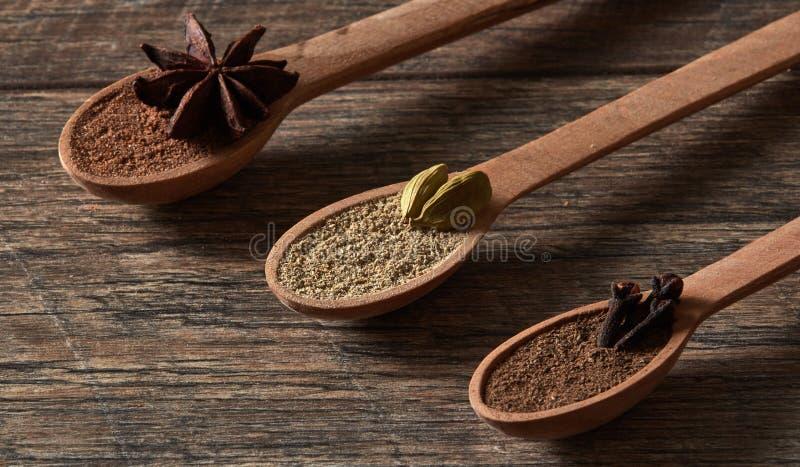 Cardamome, clous de girofle, anis d'étoile Épices moulues dans des cuillères en bois Dif images libres de droits