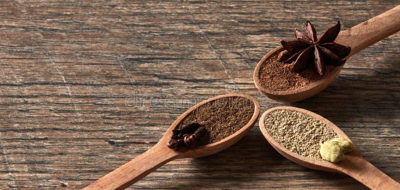 Cardamome, clous de girofle, anis d'étoile Épices moulues dans des cuillères en bois Dif photographie stock
